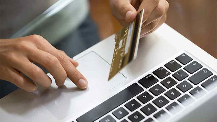 person-holds-credit-card-over-keyboard